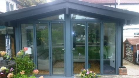 Grey bi-fold doors in a pitched roof conservatory
