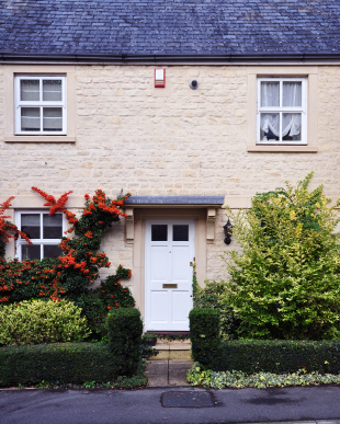 Classic home facade with timber doors and windows, grey roof and green garden
