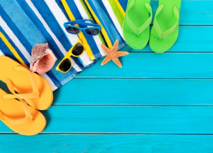 Bright and colourful summer holiday scene: flip flops, towel, sunglasses, shell, starfish.
