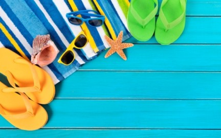 Bright and colourful summer holiday scene: flip flops, towel, sunglasses, shell, starfish