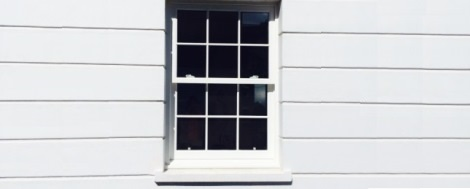 Sash window by Premier Windows in London. White windows on cladding with Georgian bars.