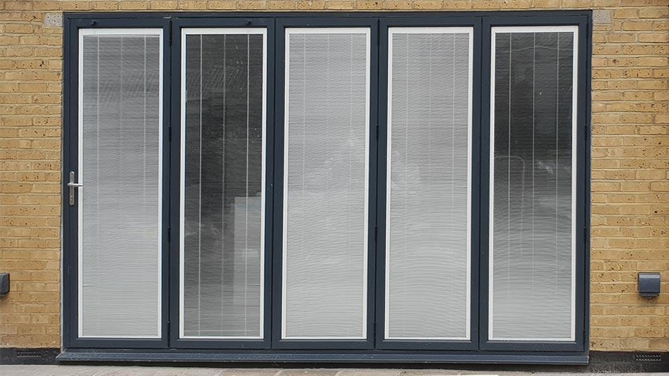 Bi-folding doors with blinds inside glass